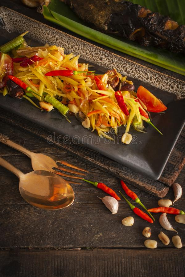 Os tailandeses do tum do som da salada da papaia na placa preta quadrada colocada na tabela de madeira lá são feijão, peixe grelh imagens de stock