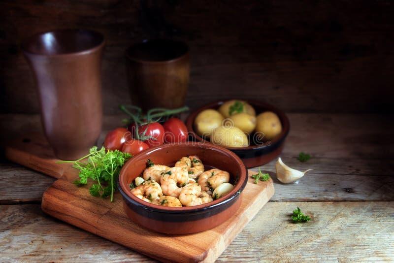 Os Tapas rolam com camarões ou camarões no azeite do alho, batatas, fotos de stock royalty free