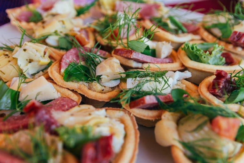 Os Tartlets com salsicha, queijo, peixes e verdes, ovos encontram-se em uma placa snacks foto de stock royalty free