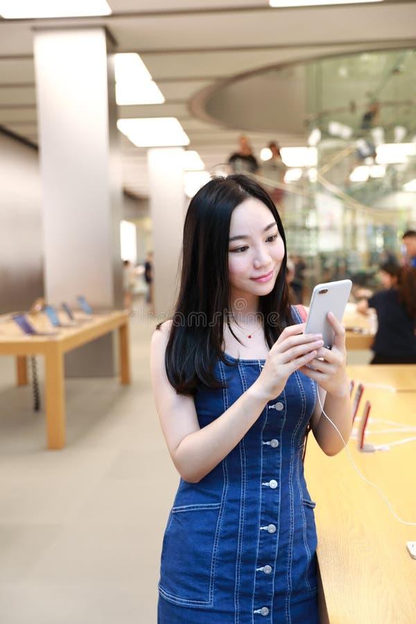 Os telefones celulares na moda novos orientais orientais chineses felizes da compra da menina da mulher de Ásia na loja de Apple  imagens de stock