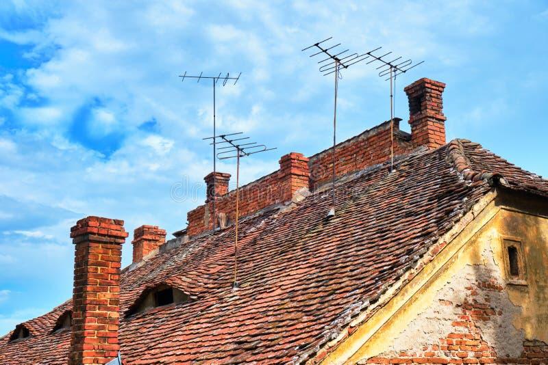 Os telhados tradicionais em Sibiu, Romênia, com olho deram forma a janelas, a chaminés do tijolo e a antenas velhas da tevê na pa imagens de stock