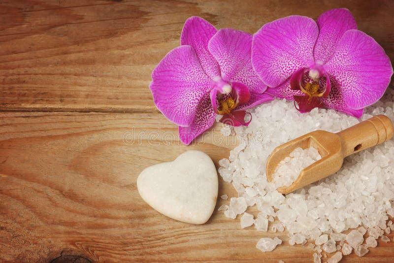 Os termas ajustados com sal do mar branco, a espátula de madeira e a orquídea brilhante florescem, coração-deram forma à pedra imagens de stock