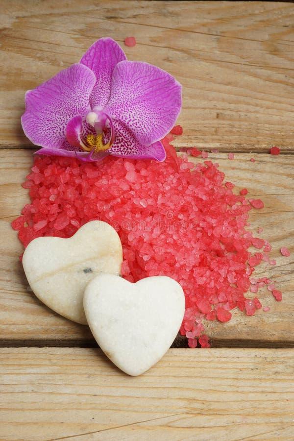Os termas ajustaram-se com sal do Mar Vermelho, a flor brilhante da orquídea e as pedras sob a forma dos corações imagem de stock royalty free
