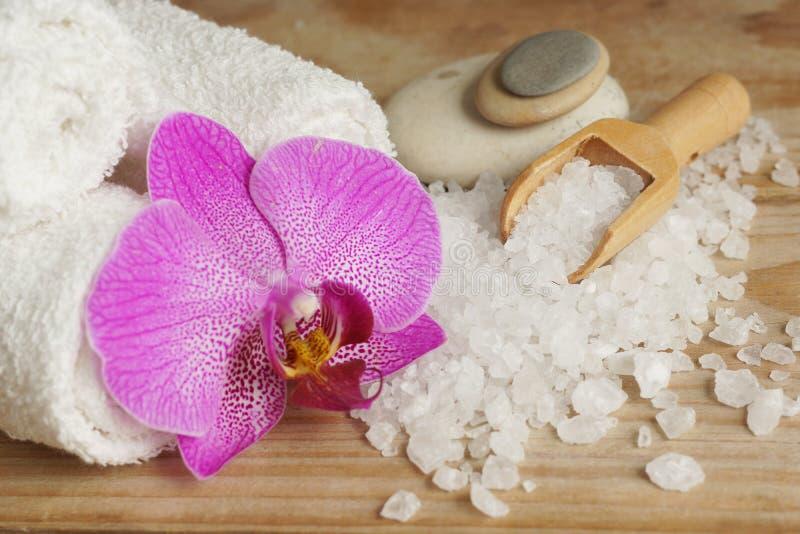 Os termas ajustaram-se com toalhas brancas, sal do mar, a espátula de madeira e a flor brilhante da orquídea imagens de stock