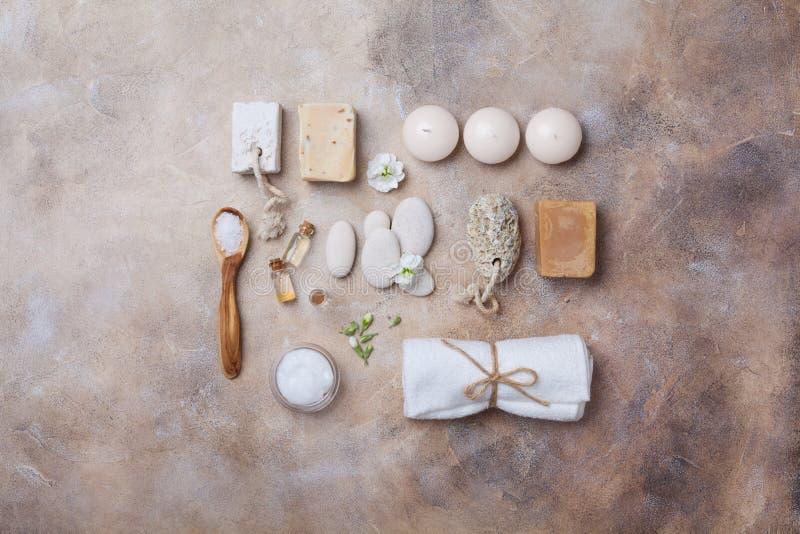 Os termas e o ajuste da beleza do sabão feito a mão, banho esfregam, velas, óleo e flores decoradas toalha na opinião superior do imagem de stock