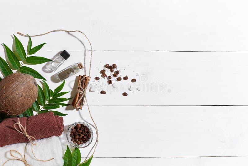 Os termas naturais ajustaram-se com feijões de café, canela, sal do mar, óleo, toalha marrom, coco e o verde sae em de madeira br fotos de stock royalty free