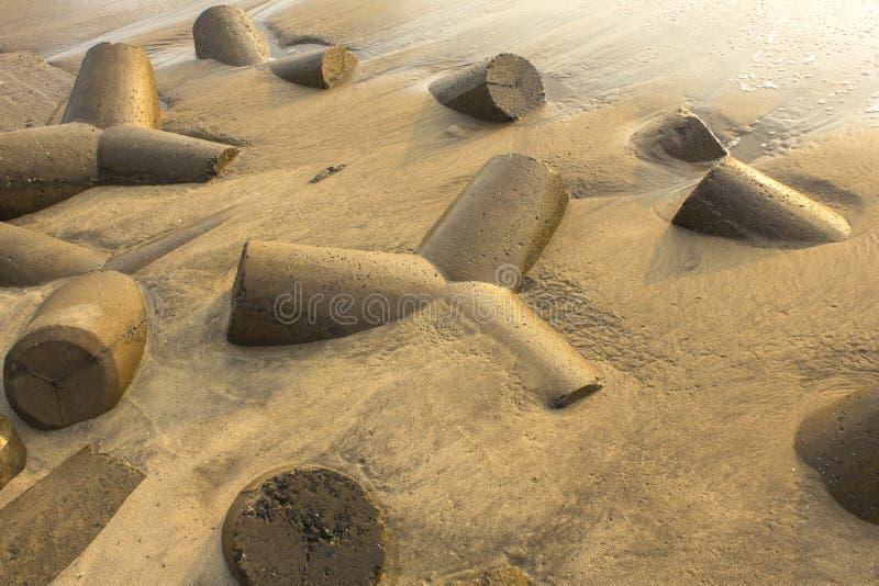 Os tetrapods concretos cinzentos projetam-se da areia amarela molhada Barreira do tsunami foto de stock