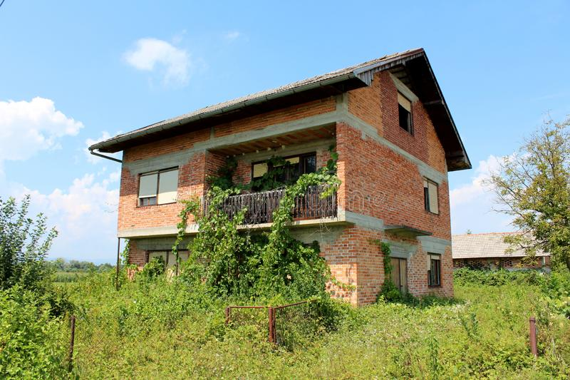 Os tijolos vermelhos abandonaram a casa da família com janelas quebradas e a cerca de fio dianteira cobertos de vegetação com as  fotografia de stock royalty free