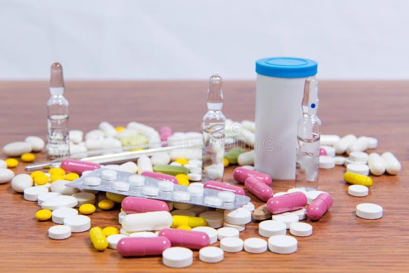 Os tipos diferentes de drogas são dispersados na tabela Tratamento das doenças com métodos modernos Homeopaticamente e produtos q imagens de stock royalty free