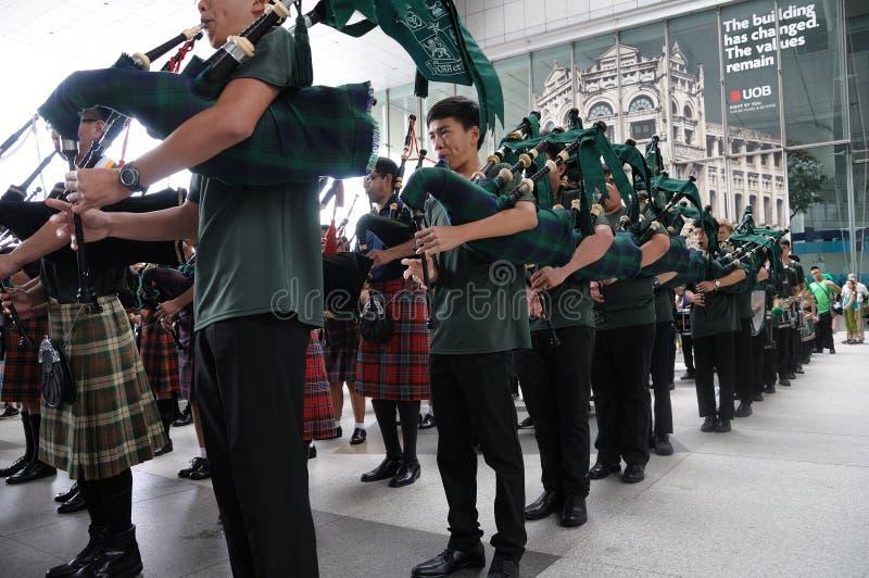 Os tocadores de gaita de foles unem recolhimentos na plaza de UOB em Singapura durante o dia 2018 do ` s de St Patrick fotografia de stock royalty free