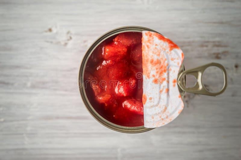 Os tomates desbastados no metal podem na opinião de tampo da mesa de madeira branca imagem de stock