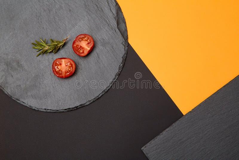 Os tomates e os alecrins maduros de cereja compuseram em placas pretas da ardósia no fundo colorido imagens de stock royalty free