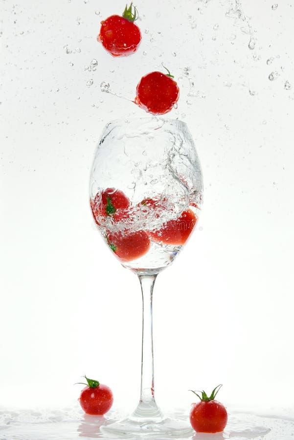 Os tomates vermelhos frescos estão saltando de um vidro de vidro foto de stock royalty free