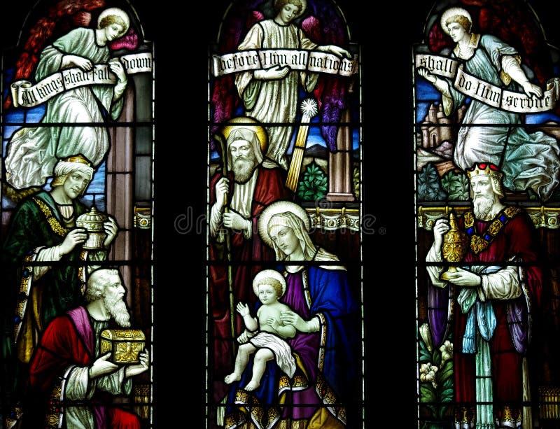 Os três reis que visitam o bebê Jesus com presentes no vitral fotografia de stock