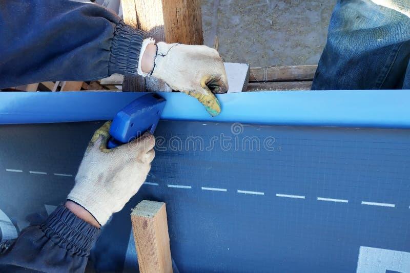 Os trabalhadores aquecem o telhado do telhado sob o filme do telhado imagem de stock royalty free