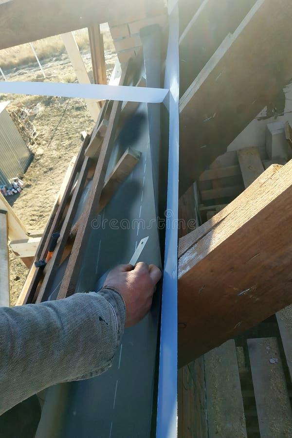 Os trabalhadores colam a fita adesiva nas vigas do telhado e unem-lhe um hydroscope imagem de stock royalty free