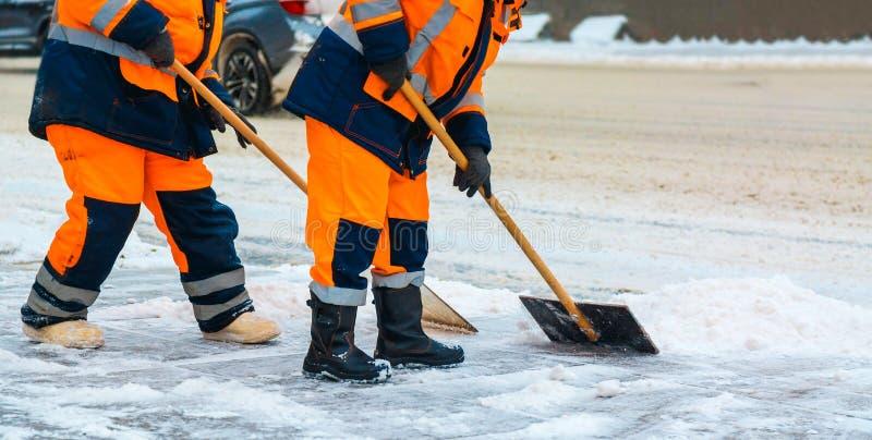 Os trabalhadores comunais dos serviços varrem a neve da estrada no inverno, em ruas de limpeza da cidade e em estradas após a tem fotografia de stock royalty free