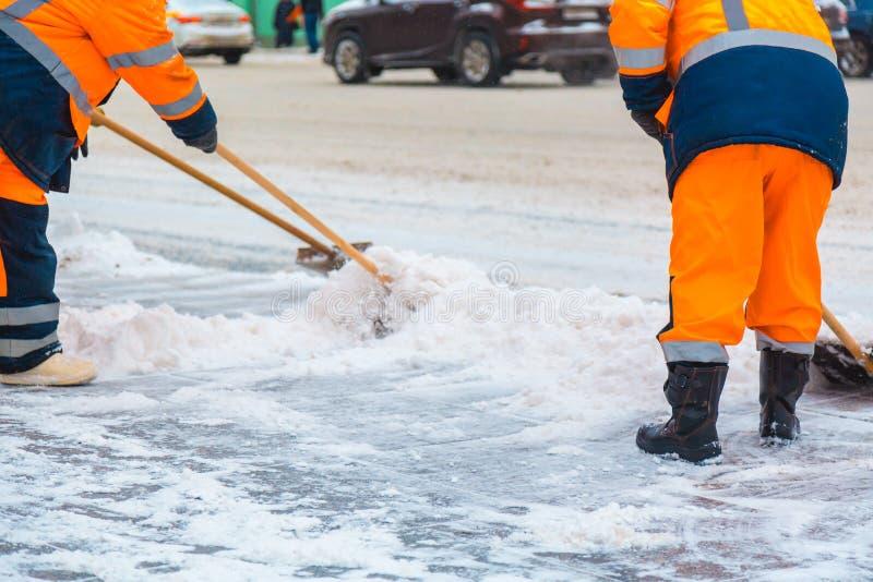 Os trabalhadores comunais dos servi?os varrem a neve da estrada no inverno, em ruas de limpeza da cidade e em estradas ap?s a tem foto de stock