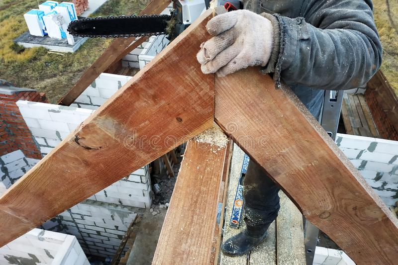 Os trabalhadores cortaram as vigas no telhado da casa da serra de cadeia imagens de stock