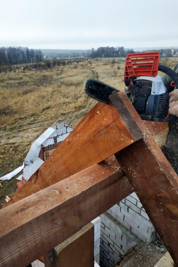 Os trabalhadores cortaram as vigas no telhado da casa da serra de cadeia imagem de stock royalty free