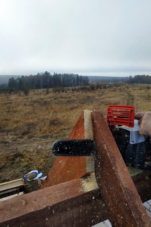 Os trabalhadores cortaram as vigas no telhado da casa da serra de cadeia fotografia de stock royalty free