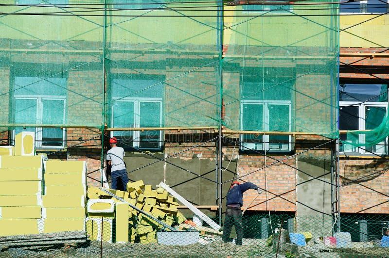 Os trabalhadores da construção emplastram a fachada da construção Restauração da casa imagem de stock