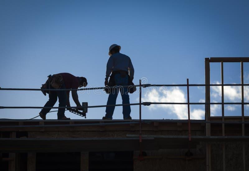 Os trabalhadores da construção mostram em silhueta no telhado imagem de stock royalty free