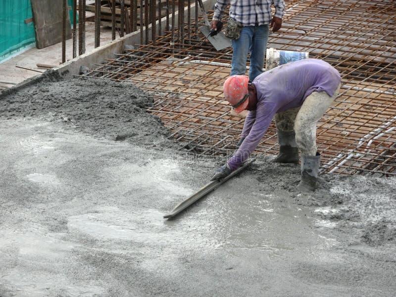 Os trabalhadores da construção que nivelam o concreto molhado foram derramados imagens de stock royalty free