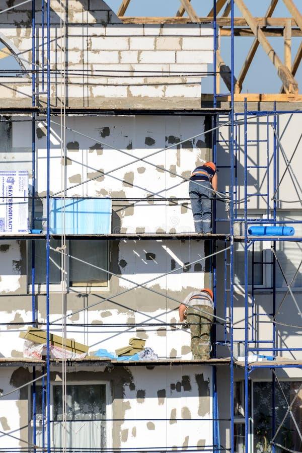 Os trabalhadores da construção realizam o trabalho na construção do emplastro e da isolação foto de stock