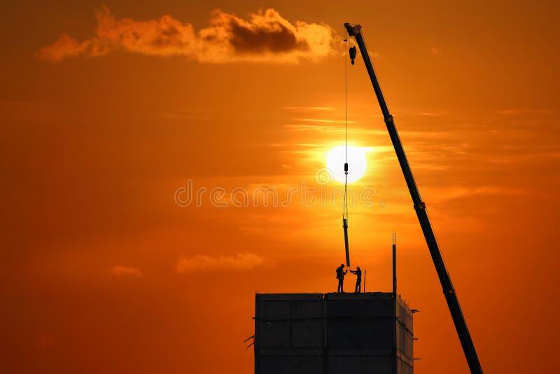 Os trabalhadores da construção da silhueta estão trabalhando sobre a estrutura de construção com céu do nascer do sol fotografia de stock royalty free
