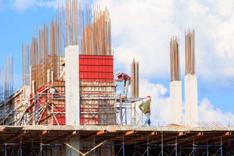 Os trabalhadores da construção situam e construção do alojamento no trabalho do trabalhador exterior qual manda o fundo do céu co foto de stock