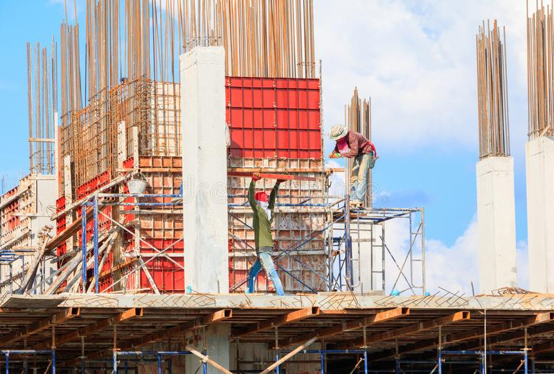 Os trabalhadores da construção situam e construção do alojamento no trabalho do trabalhador exterior qual manda o fundo do céu co imagens de stock