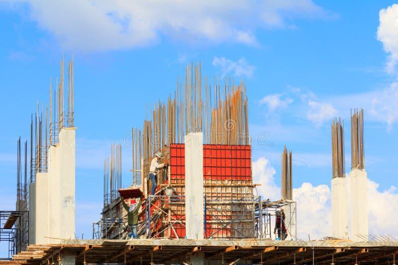 Os trabalhadores da construção situam e construção do alojamento no trabalho do trabalhador exterior qual manda o fundo do céu co fotografia de stock