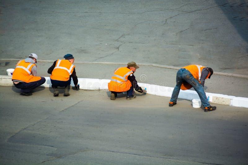 Os trabalhadores da estrada estão pintando o lancil Para trás vista em diversos povos fotografia de stock