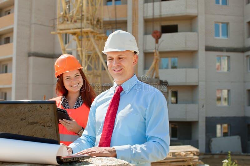 Os trabalhadores de colar branco trabalham no terreno de construção imagens de stock royalty free