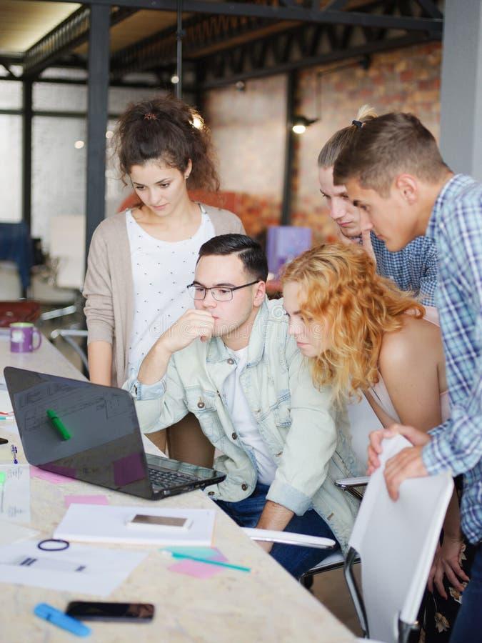 Os trabalhadores de escritório reveem planos e projetos no portátil foto de stock