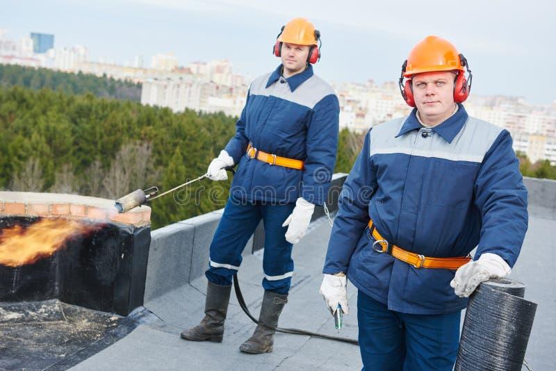 Os trabalhadores de telhado liso com telhado do betume sentiram e tocha da chama imagens de stock