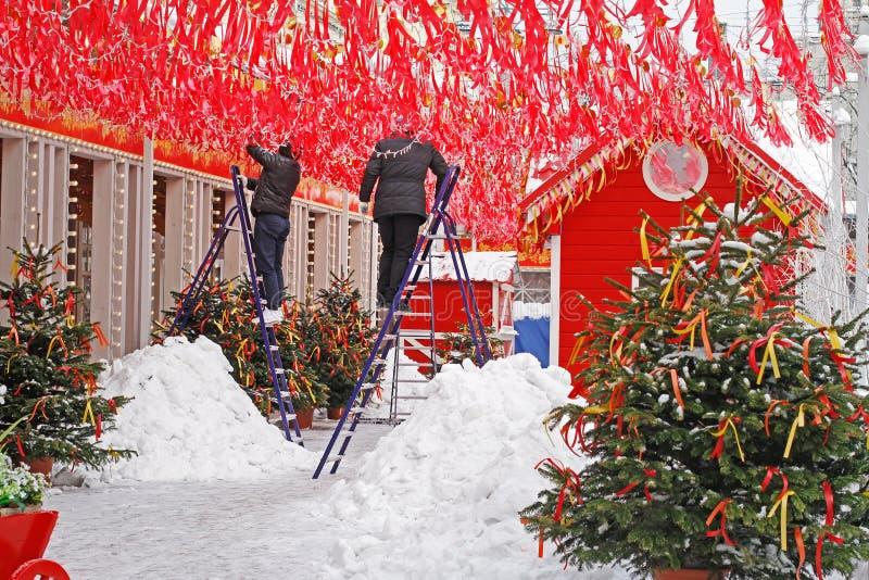 Os trabalhadores decoram o quadrado de Tverskaya com fitas vermelhas e as festões para o festival nacional do russo 'Shrove 'em M fotografia de stock royalty free