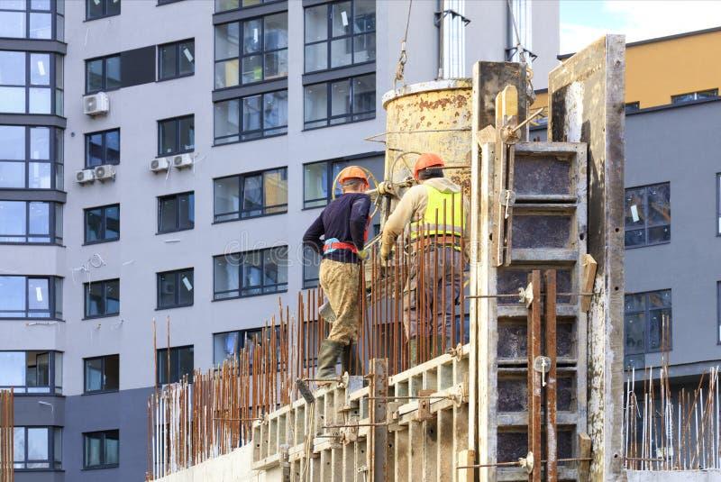 Os trabalhadores derramam concreto em uma construção da casa imagem de stock