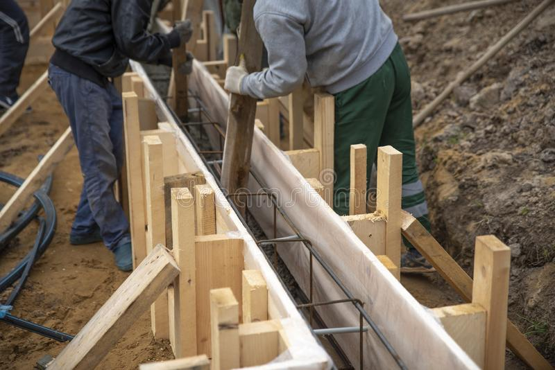 Os trabalhadores derramam concreto na funda??o foto de stock royalty free