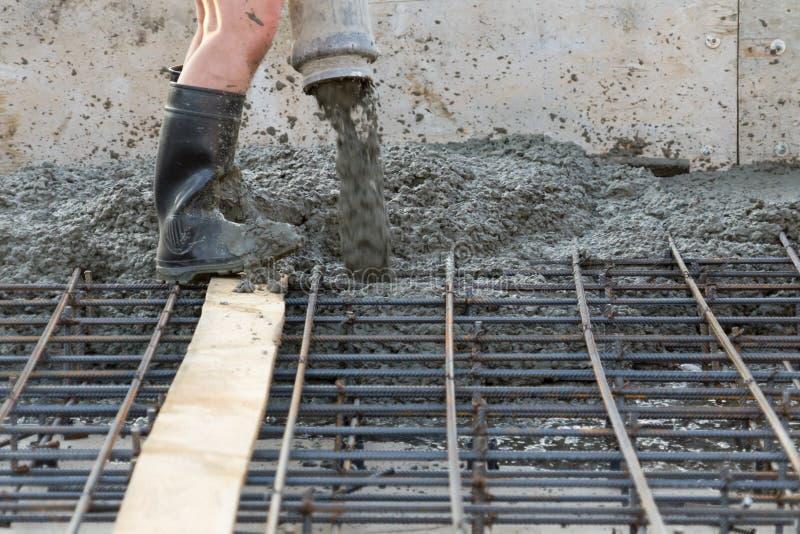 Os trabalhadores derramam a fundação para a construção de uma construção residencial foto de stock royalty free