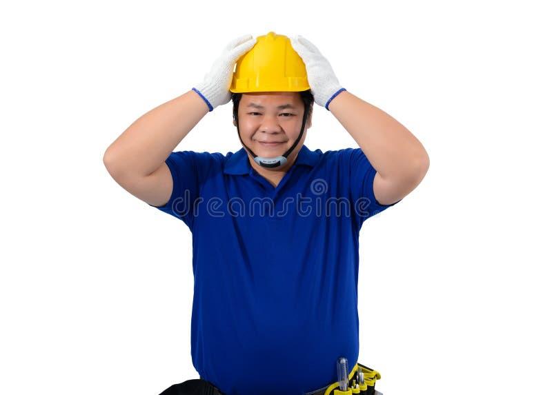 Os trabalhadores do homem da construção na camisa azul com luvas protetoras, no capacete com correia da ferramenta e nas duas mão fotografia de stock royalty free