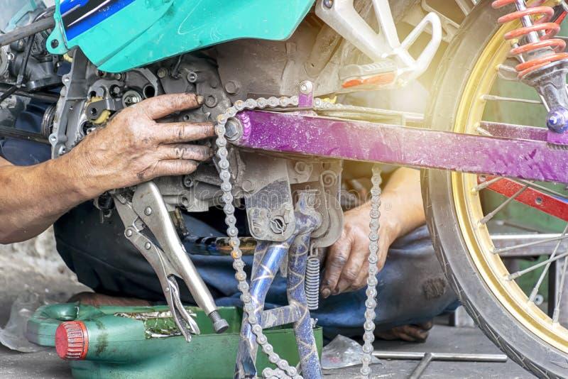 Os trabalhadores do reparo do motor da motocicleta estão trabalhando duramente fotografia de stock