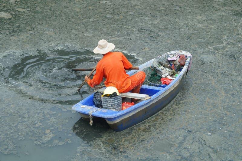 Os trabalhadores do saneamento limpam os desperdícios no rio foto de stock royalty free