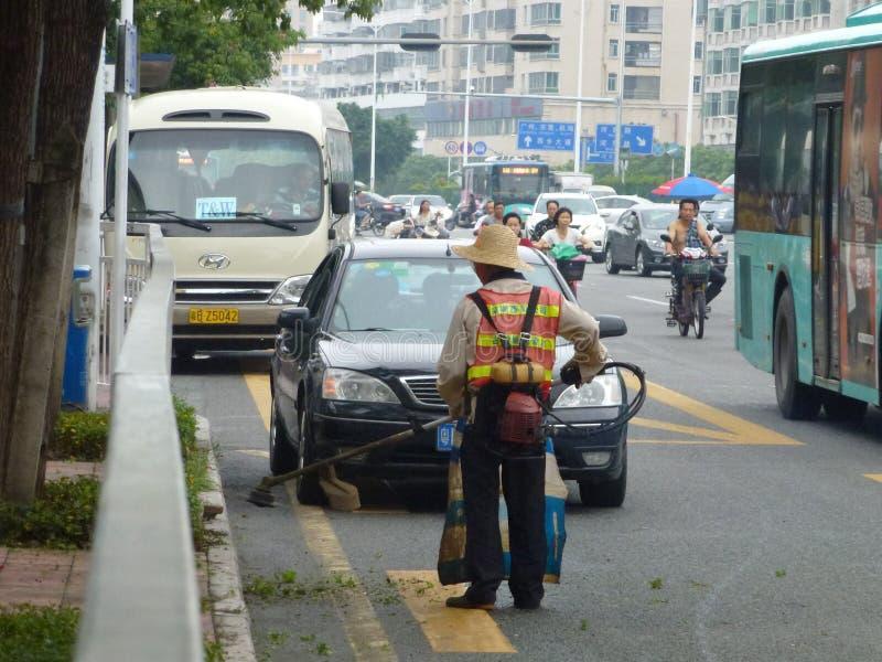 Os trabalhadores do saneamento na remoção da borda da estrada removem ervas daninhas imagens de stock