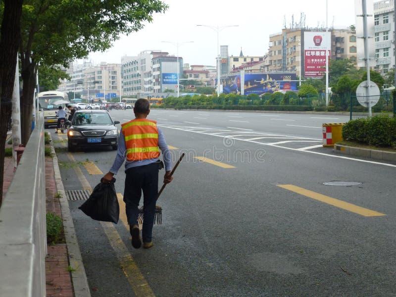 Os trabalhadores do saneamento na remoção da borda da estrada removem ervas daninhas foto de stock royalty free