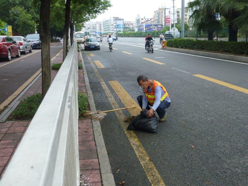 Os trabalhadores do saneamento na remoção da borda da estrada removem ervas daninhas imagem de stock
