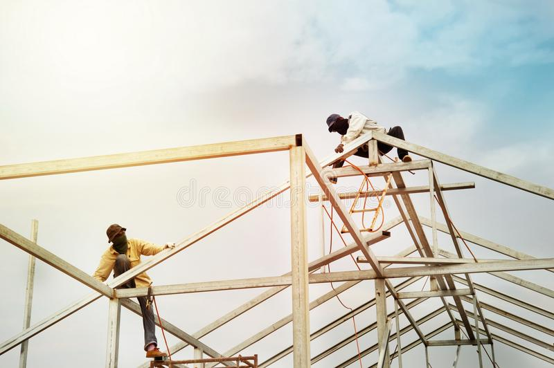 Os trabalhadores dos homens na construção de aço do telhado estruturam a indústria com imagens de stock