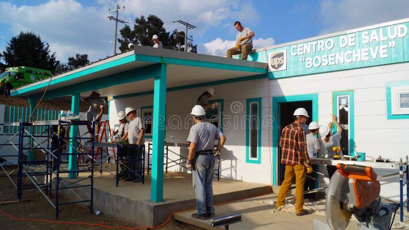 Os trabalhadores dos trabalhos de equipa constroem um centro do médico fotos de stock