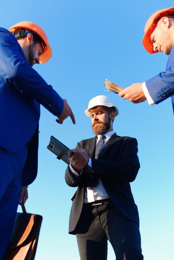 Os trabalhadores e os coordenadores realizam a reunião sobre o fundo do céu azul foto de stock